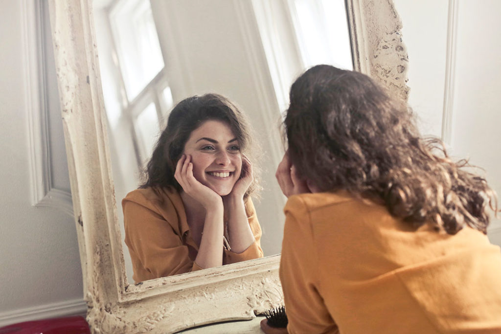 woman looking in the mirror  thinking about get older